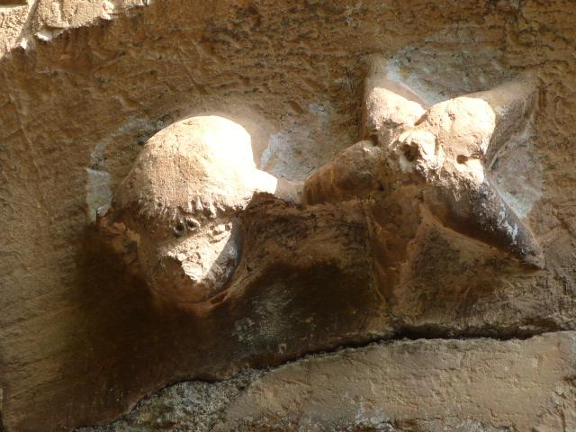 Motifs sous le cadran canonial de la porte de l'église